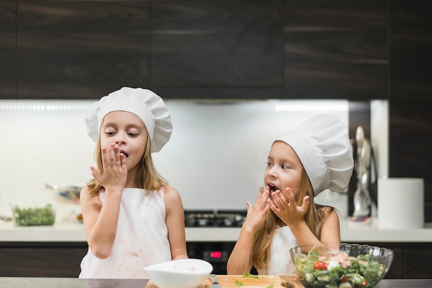 Portrait of two sisters licking their hands while preparing food