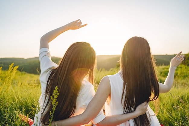 Portrait of two sisters in white dresses with long hair in a field
