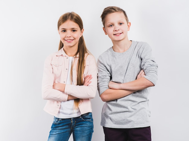 Portrait of two smiling boy and girl with their arms crossed looking to camera against white background