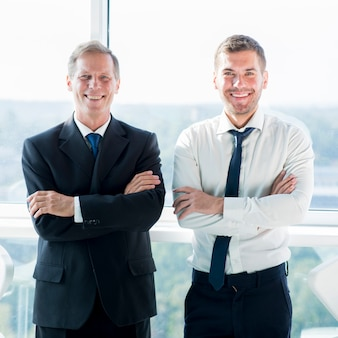 Portrait of two smiling businessmen standing near the window