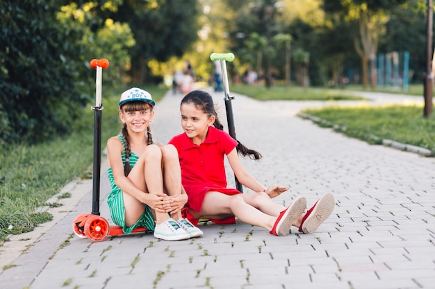 Portrait of two smiling female friends sitting on push scooter