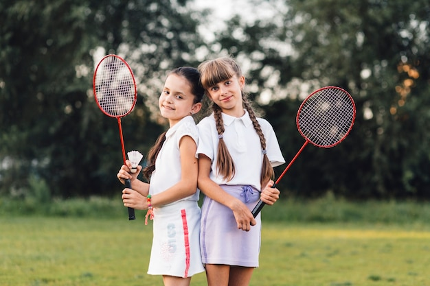 Portrait of two smiling girls holding shuttlecock and badminton in hand