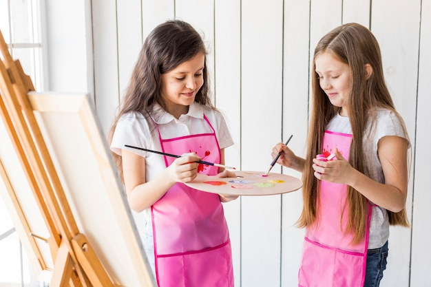 Portrait of two smiling girls standing near the easel mixing the paint with brushes on palette