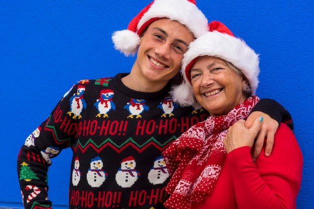 Portrait of two smiling people, grandmother and teenager grandson wearing santa hat and christmas sweater, hugging each other and smiling looking at camera. positive emotion and family concept