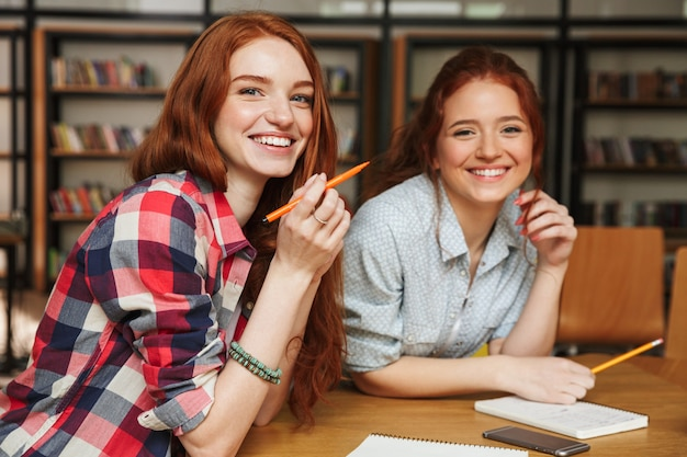 Portrait of a two smiling teenage girls doing