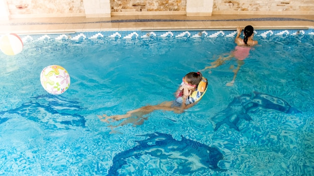 Portrait of two smiling teenage girls swimming in pool at gym