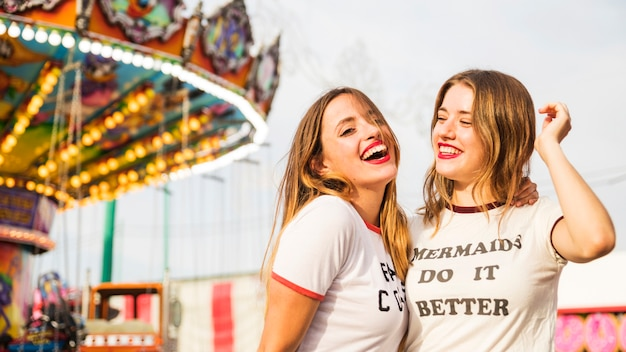 Portrait of two smiling young woman at amusement park