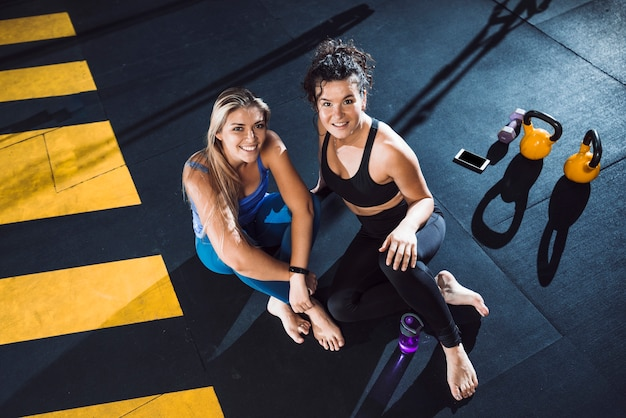 Portrait of two smiling young woman sitting in fitness club