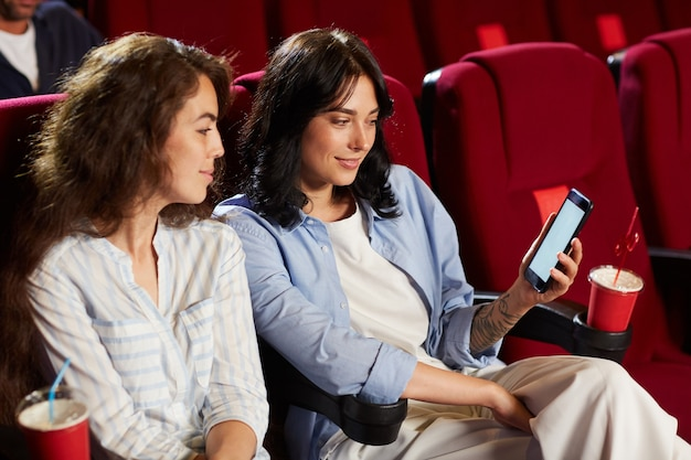 Portrait of two smiling young women holding smartphone with blank screen while enjoying movie in cinema theater, copy space