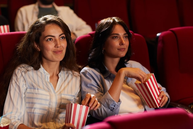 Portrait of two smiling young women watching movie in cinema and eating popcorn while sitting on red velvet seats, copy space