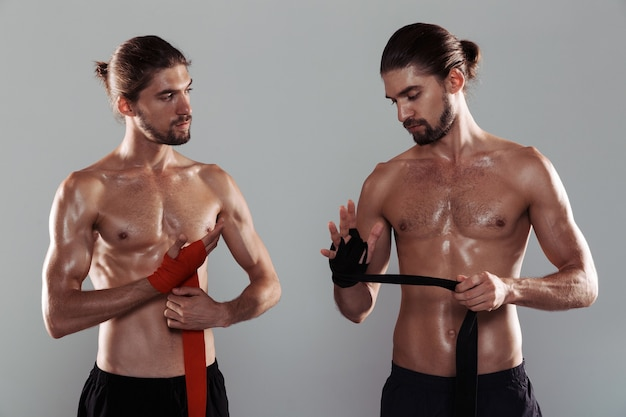 Portrait of a two sporty muscular shirtless twin brotherss