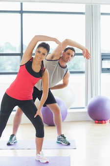 Portrait of two sporty people stretching hands at yoga class