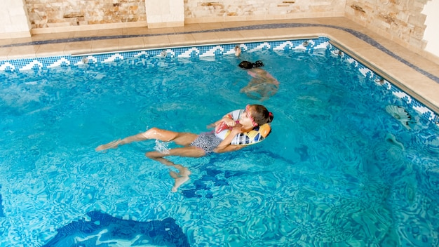 Portrait of two teenage girls friends swimming and having fun in indoors swimming pool