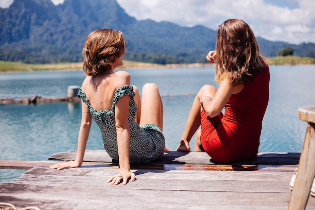 Portrait of two woman tourist friends in summer dresses on vacation travel around thailand khao sok lake with beautiful mountain view.