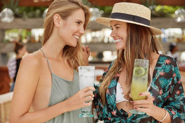Ritratto di due donne si incontrano nella caffetteria all'aperto, tintinnano bicchieri con cocktail freddi, si guardano con espressioni positive. le femmine abbastanza rilassate si rilassano durante la festa, si divertono insieme
