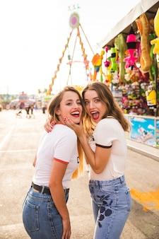 Portrait of two women making fun at amusement park