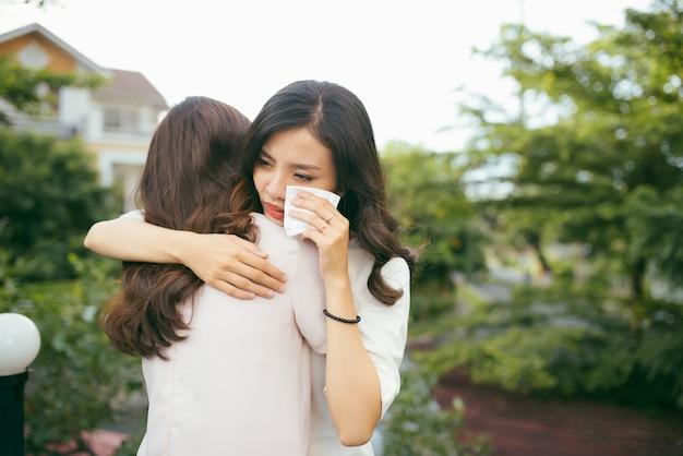 Портрет двух женщин. грустная несчастная молодая женщина утешает своего друга. дружба помогает поддерживать и концепции трудных времен. человеческие эмоции, чувства