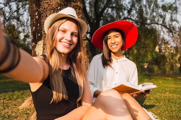 Portrait of two women take a selfie in the park while reading a book
