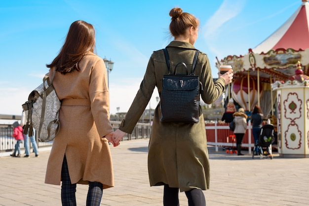 Portrait of two women with back, walk down the street in coats and backpacks and hold hands