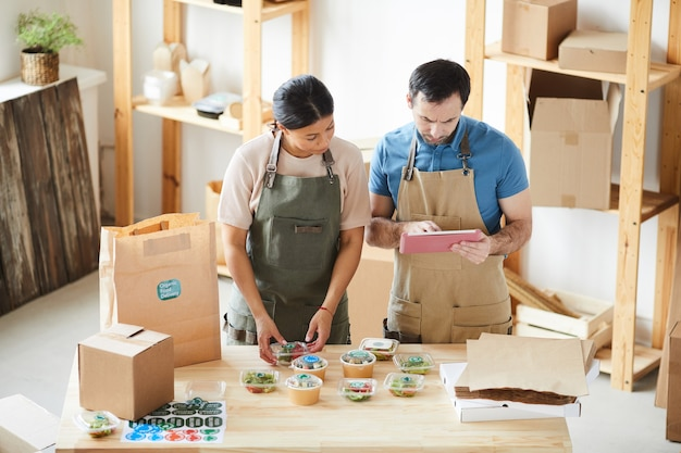 Portrait of two workers wearing aprons packaging orders at wooden table in food delivery service
