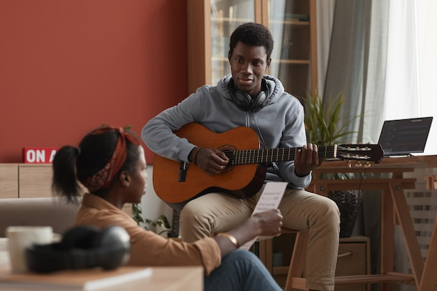 Portrait of two young african-american musicians playing guitar and writing music together in home recording studio