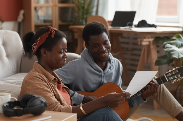 Portrait of two young african-american musicians playing guitar and writing music together while sitting on floor in recording studio, copy space