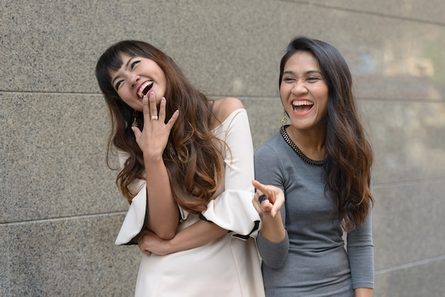 Portrait of two young asian businesswomen together in the city outdoors