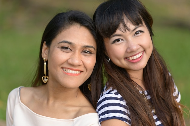 Portrait of two young asian women together relaxing at the park outdoors