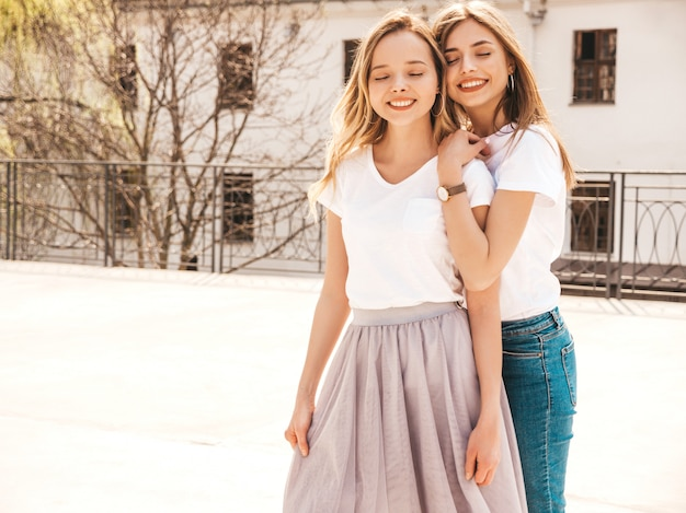 Portrait of two young beautiful blond smiling hipster girls in trendy summer white t-shirt clothes.   . positive models having fun.hugging