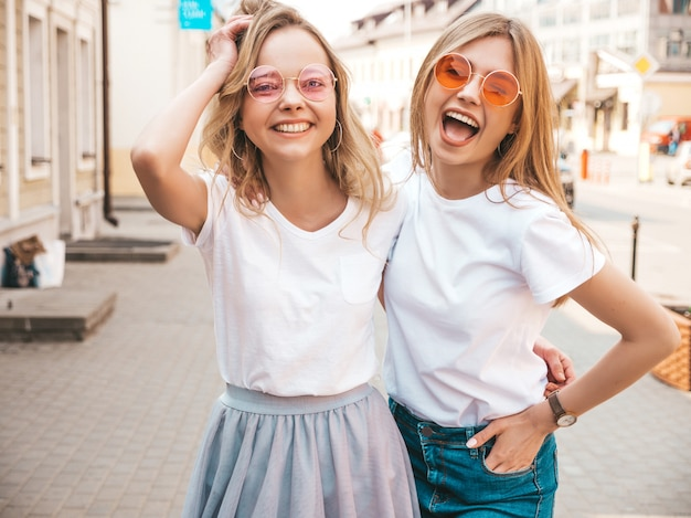 Portrait of two young beautiful blond smiling hipster girls in trendy summer white t-shirt clothes.   . positive models having fun in sunglasses.hugging