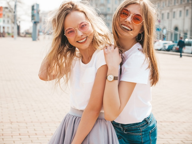 Portrait of two young beautiful blond smiling hipster girls in trendy summer white t-shirt clothes.