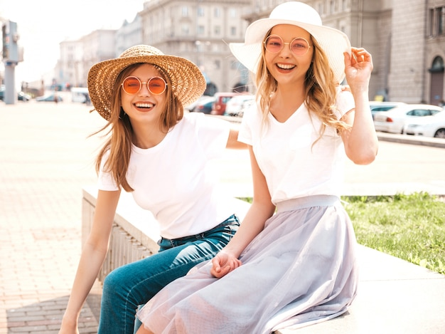 Portrait of two young beautiful blond smiling hipster girls in trendy summer white t-shirt clothes.  .