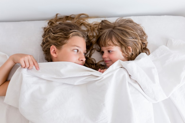 Portrait of two young beautiful kids resting on bed, smiling and covering with sheets. white room.