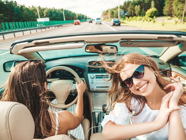 Portrait of two young beautiful and smiling hipster female in convertible car