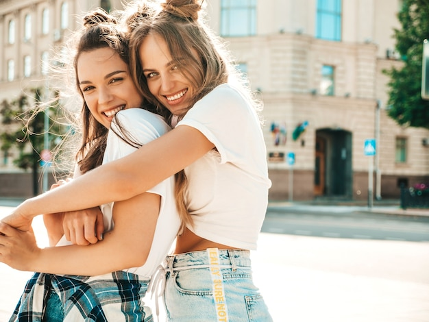 Portrait of two young beautiful smiling hipster female in trendy summer white t-shirt clothes