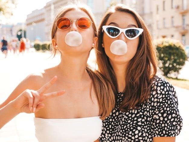 Ritratto di due giovani belle ragazze sorridenti hipster in abiti estivi alla moda