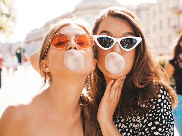 Portrait of two young beautiful smiling hipster girls in trendy summer clothes.