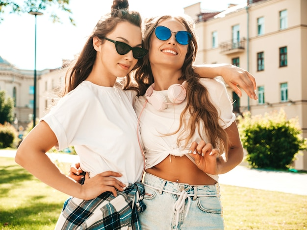 Portrait of two young beautiful smiling hipster girls in trendy summer white t-shirt clothes