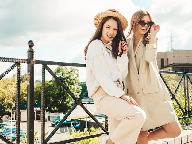 Portrait of two young beautiful smiling hipster girls in trendy white sweater and coat