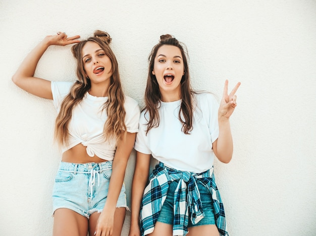 Portrait of two young beautiful smiling hipster women in trendy summer white t-shirt clothes