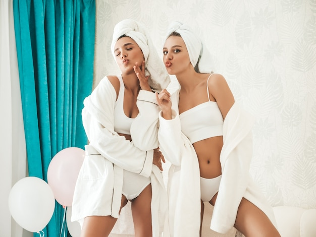 Portrait of two young beautiful smiling women in white bathrobes and towels on head