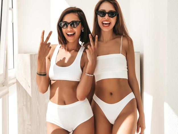 Ritratto di due giovani belle donne sorridenti in lingerie bianca