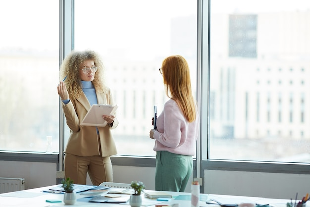 Portrait of two young businesswomen discussing work project while standing against window in modern office, copy space