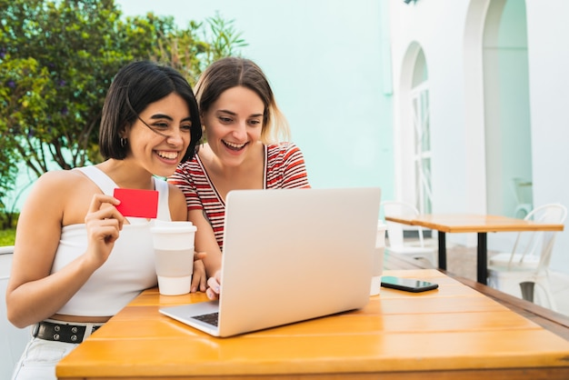 Portrait of two young friends doing online shopping with laptop and credit card at coffee shop. shop online concept.