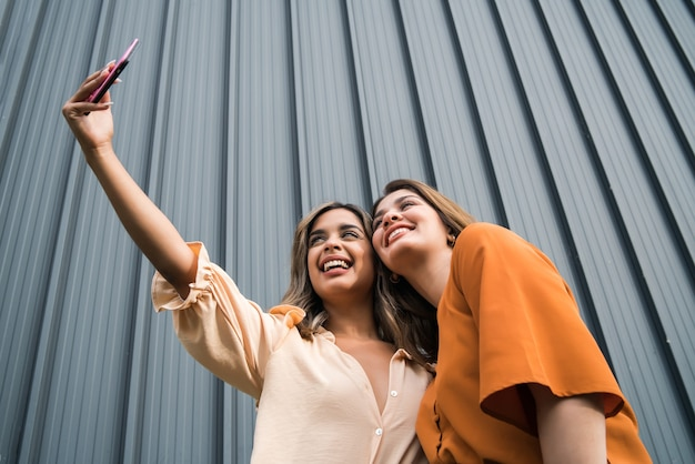 Portrait of two young friends having fun together and taking a selfie with a mobile phone outdoors. urban concept.
