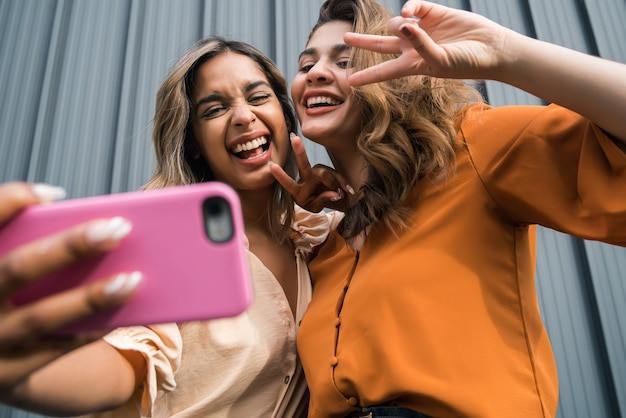 Portrait of two young friends having fun together and taking a selfie with a mobile phone outdoors