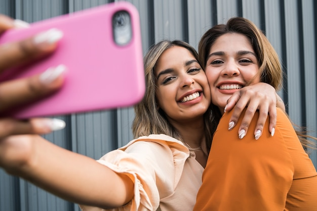 Portrait of two young friends smiling and taking a selfie with their mobile phone outdoors. urban concept.
