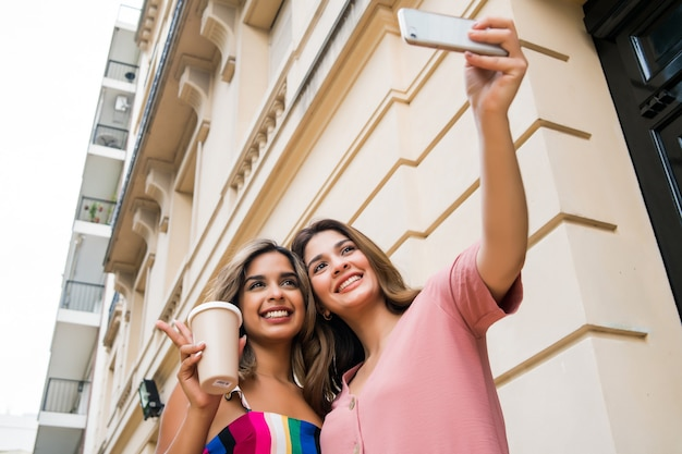Portrait of two young friends smiling and taking a selfie with their mobile phone while sitting outdoors. urban concept.