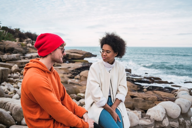 Portrait of two young friends spending good time together and having a conversation while sitting with the sea in the space.