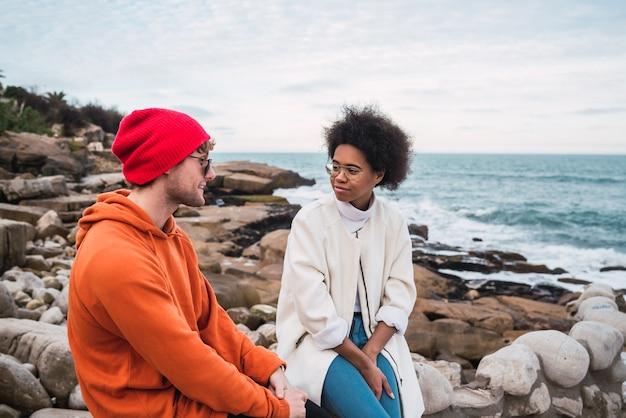 Ritratto di due giovani amici che trascorrono del buon tempo insieme e hanno una conversazione seduti con il mare nello spazio.